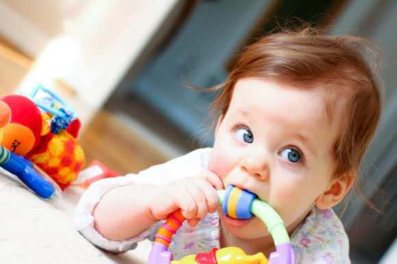 малыш с игрушкой во рту