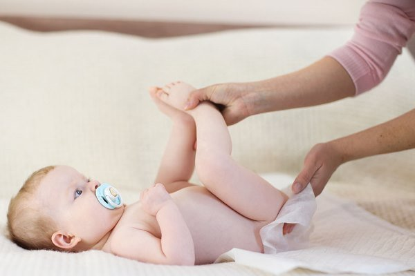 мама меняет подгузник ребенку
